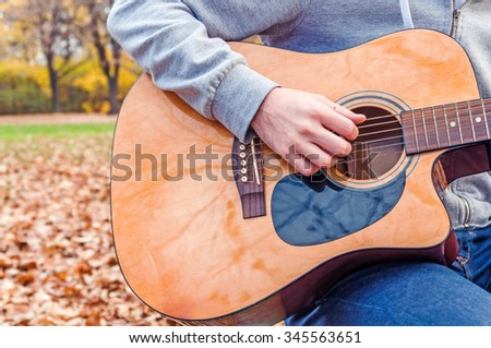 Young man playing acoustic guitar close up outdoors in autumn park - stock photo