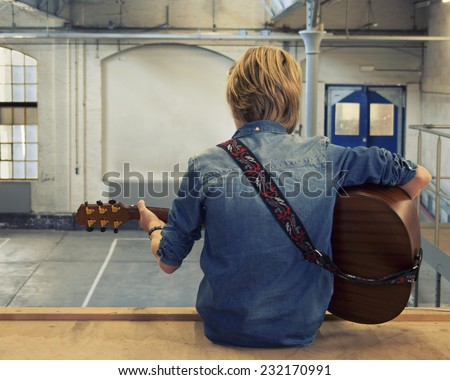 Young man playing acoustic guitar in an old factory building - stock photo