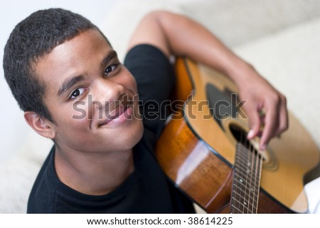 Young man playing an acoustic guitar, closeup. - stock photo