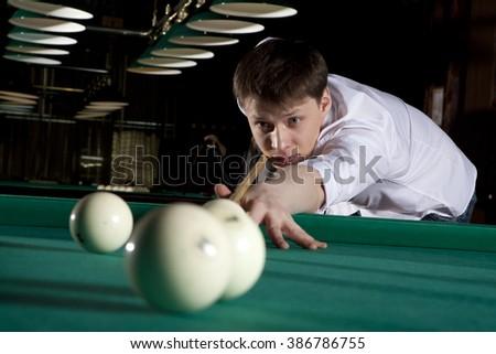Young man playing billiards in the dark billiard club - stock photo