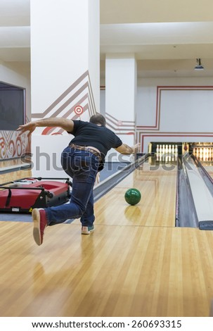 Young man playing bowling - stock photo