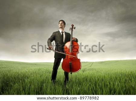 Young man playing cello on a green meadow - stock photo