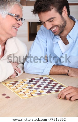 young man playing checkers with older woman - stock photo