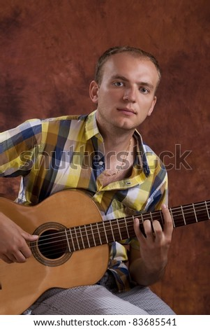 Young man playing classic spanish guitar - stock photo