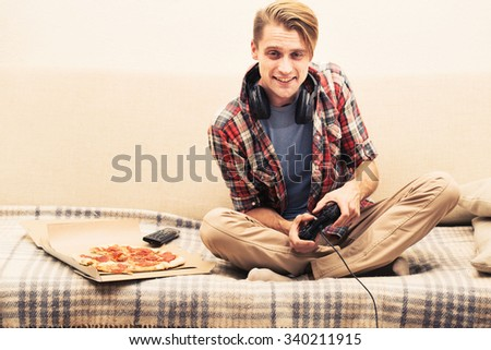 Young man playing computer game home  - stock photo
