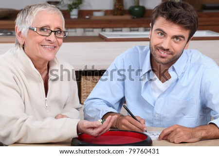 young man playing dice with older woman - stock photo