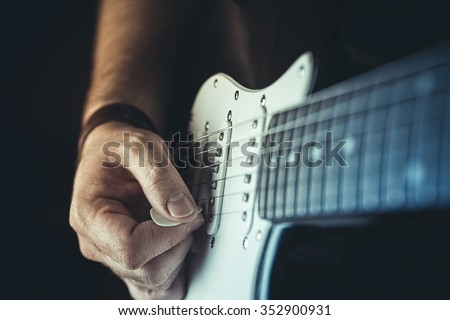 Young man playing electric guitar. Music, instrument education and learning concept - stock photo