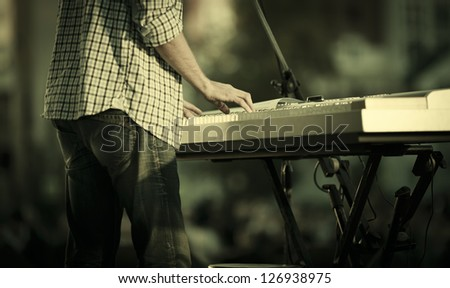 young man playing electronic keyboard, selective focus - stock photo