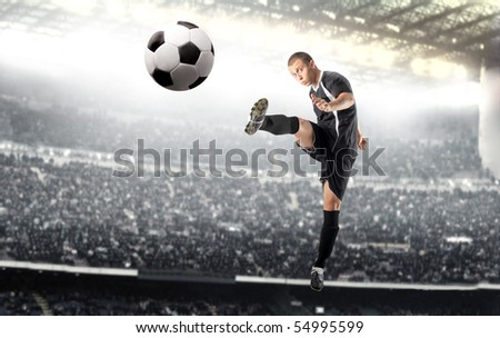 Young man playing football in a stadium - stock photo