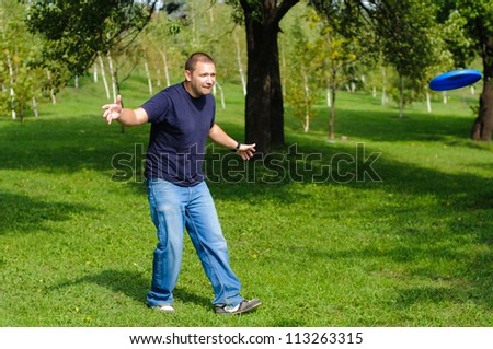 Young man playing frisbee on green grass - stock photo
