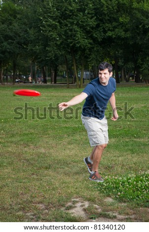young man playing frisbee outdoors - stock photo