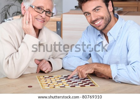 Young man playing game with elderly woman - stock photo