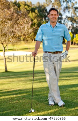 Young man playing golf leaning on the club - stock photo