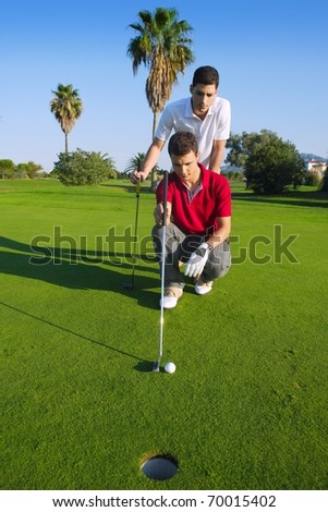 young man playing golf looking and aiming for the hole - stock photo