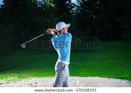 Young man playing golf outdoors - stock photo