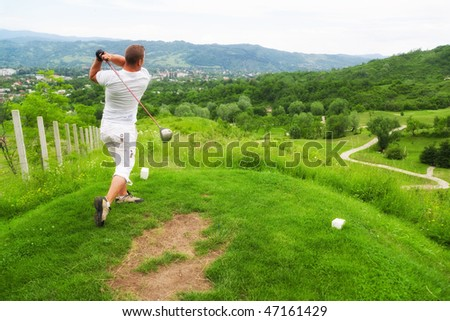 Young man playing golf outdoors.