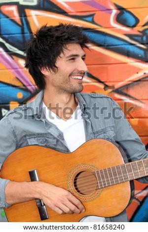 young man playing guitar - stock photo