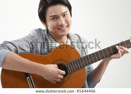 Young man playing guitar and looking at camera, portrait