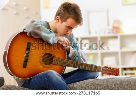 Young man playing guitar at his home - stock photo