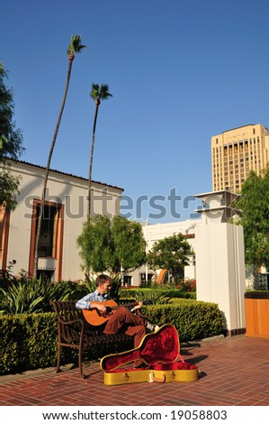 Young man playing guitar for money in a train station courtyard.