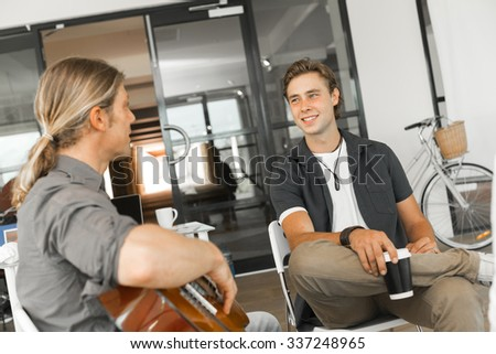 Young man playing guitar in bright room