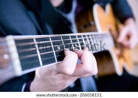 Young man playing guitar. Music, instrument education and learning concept - stock photo
