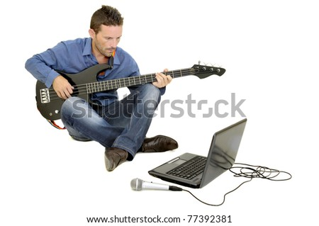 Young man playing guitar with a laptop - stock photo