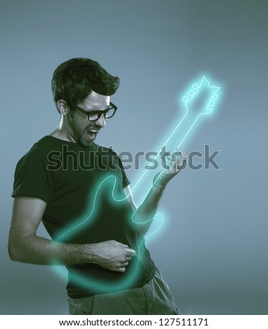 Young man playing imaginary guitar and squealing. Expressive boy on a grey background