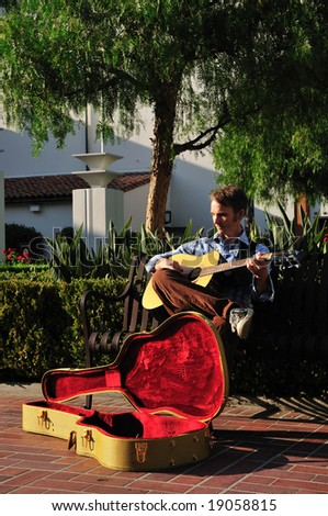 Young man playing music on his guitar for donations in a sunny courtyard.