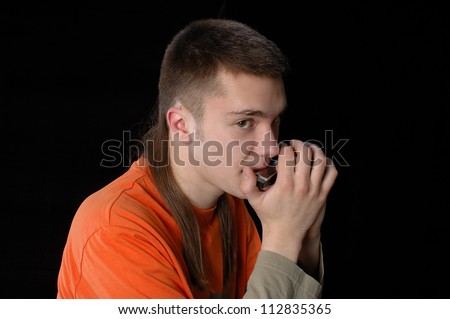 young man playing music on his harmonica on a black background ...