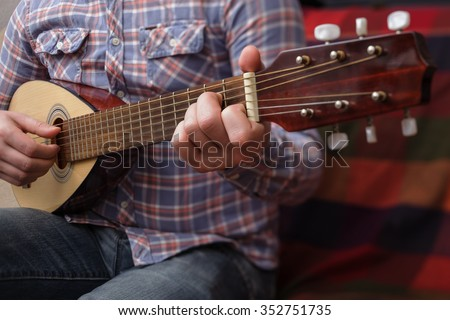 Young man playing on a small guitar