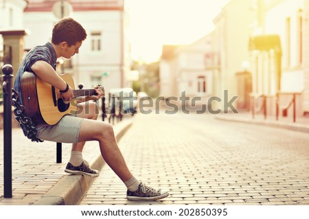Young man playing on acoustic guitar - outdoor - stock photo