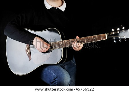Young man playing on black  guitar.