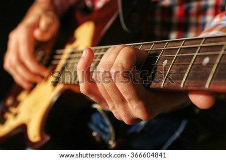 Young man playing on electric guitar close up - stock photo