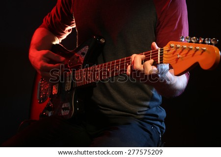 Young man playing on electric guitar on dark background - stock photo