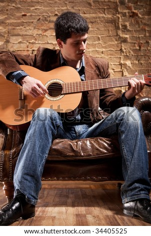 Young man playing on guitar sitting in a chair. - stock photo