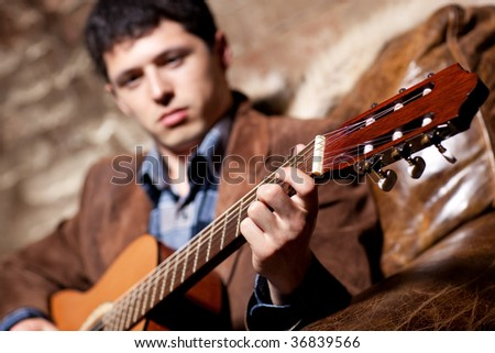 Young man playing on guitar sitting in a chair. Focus on hand. - stock photo