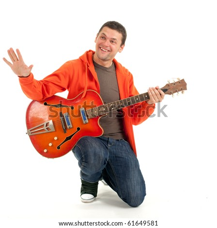 young man playing on orange electric guitar - stock photo