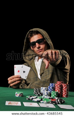Young man playing poker and holding a couple of aces against a black background - stock photo