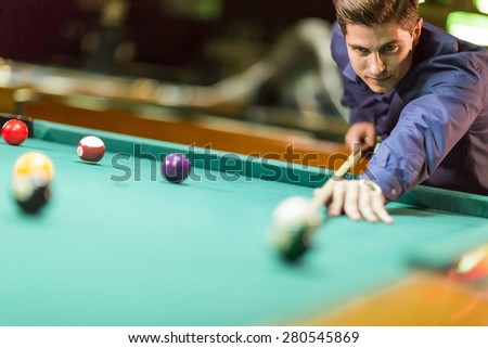 Young man playing pool - stock photo