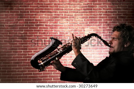 young man playing saxophone against a brick wall - stock photo
