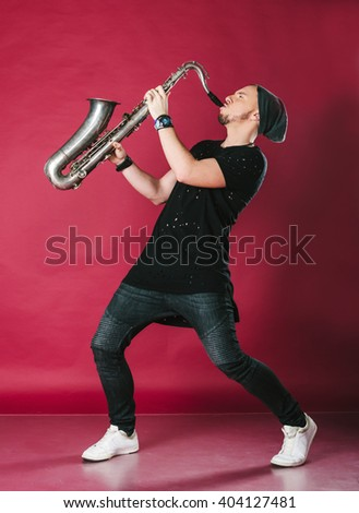 Young man playing saxophone. Man in modern clothes. Photo isolated on red background. - stock photo