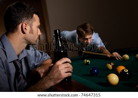 Young man playing snooker, concentrating with cue in hand, friend watching holding beer.? - stock photo