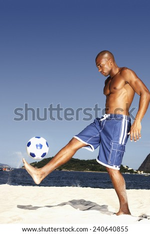 Young Man Playing Soccer on Beach - stock photo