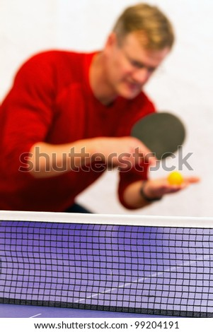 Young man playing table tennis - stock photo