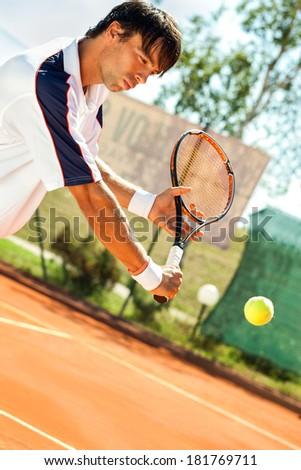 Young man playing tennis, hitting tennis ball - stock photo