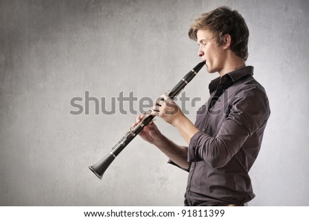 Young man playing the clarinet - stock photo