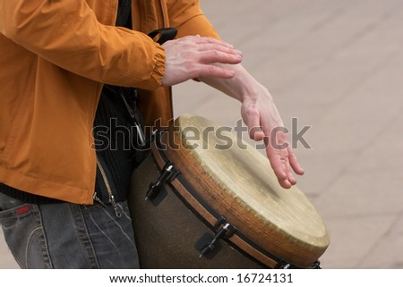 Young man playing the drums on city street - stock photo