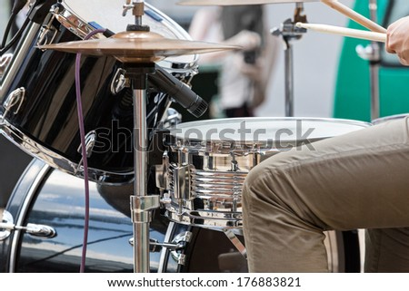 Young man playing the drums on street performance - stock photo