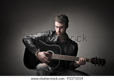 Young man playing the guitar - stock photo